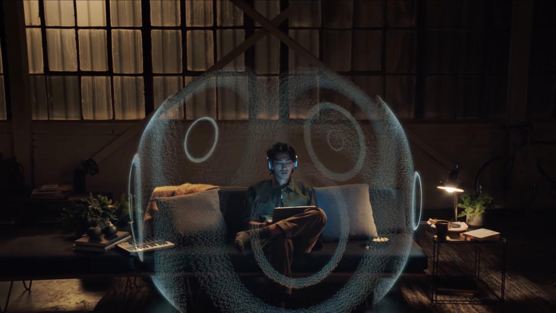 Illustration Apple pour l'audio spatial représentant un jeune homme assis sur son canapé, portant ses AirPods Max et écoutant de la musique sur iPad Pro