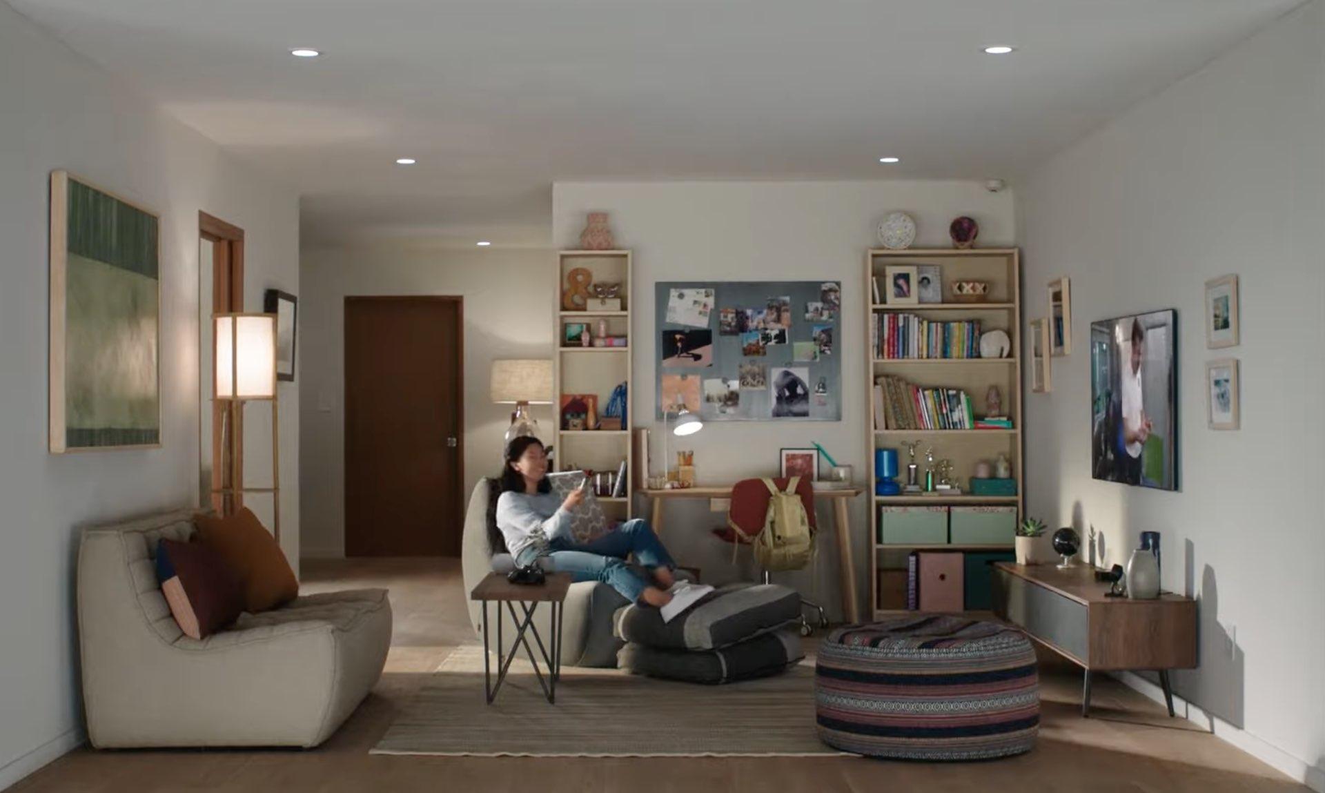 Une image de style de vie montrant une maison avec une jeune femme assise sur le canapé, souriante et regardant Apple TV et tenant Siri Remote dans sa main droite