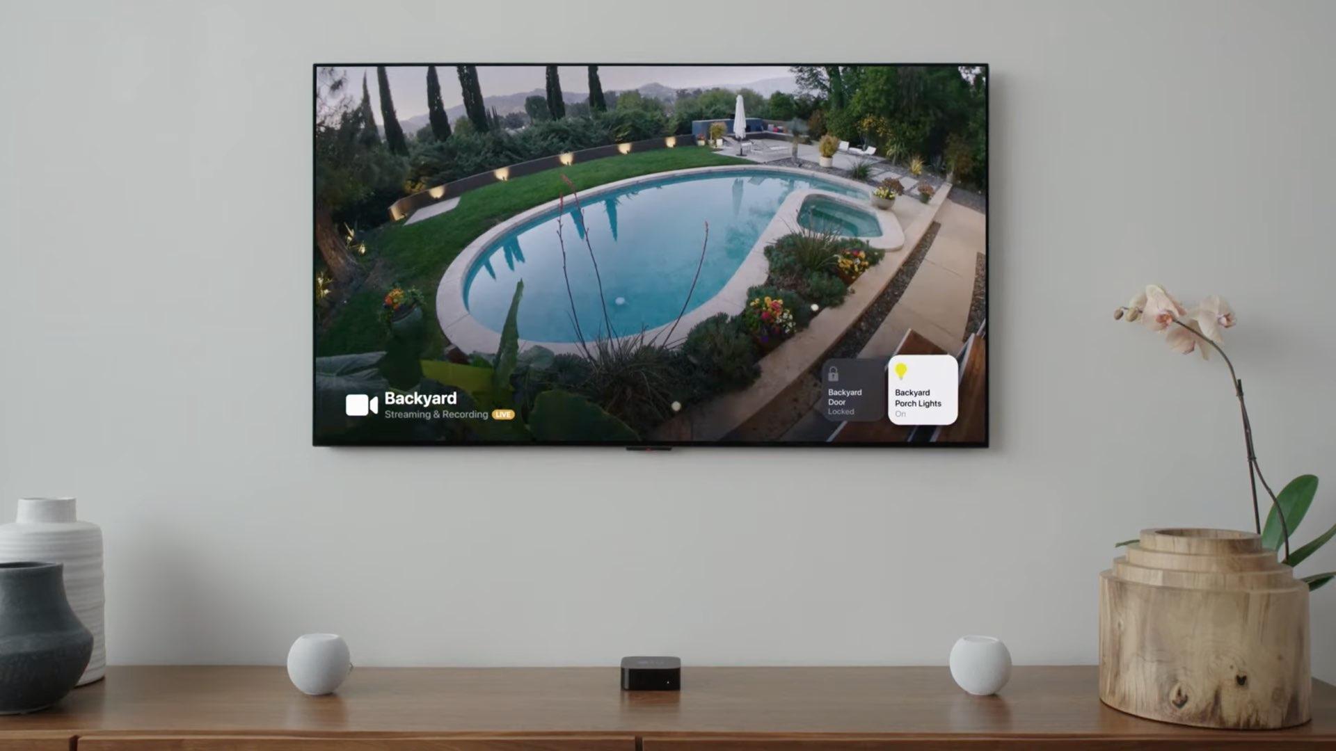Une image montrant un flux de caméra de sécurité HomeKit affiché sur Apple TV avec tvOS 15, avec des commandes d'éclairage intelligentes visibles dans les coins de l'écran